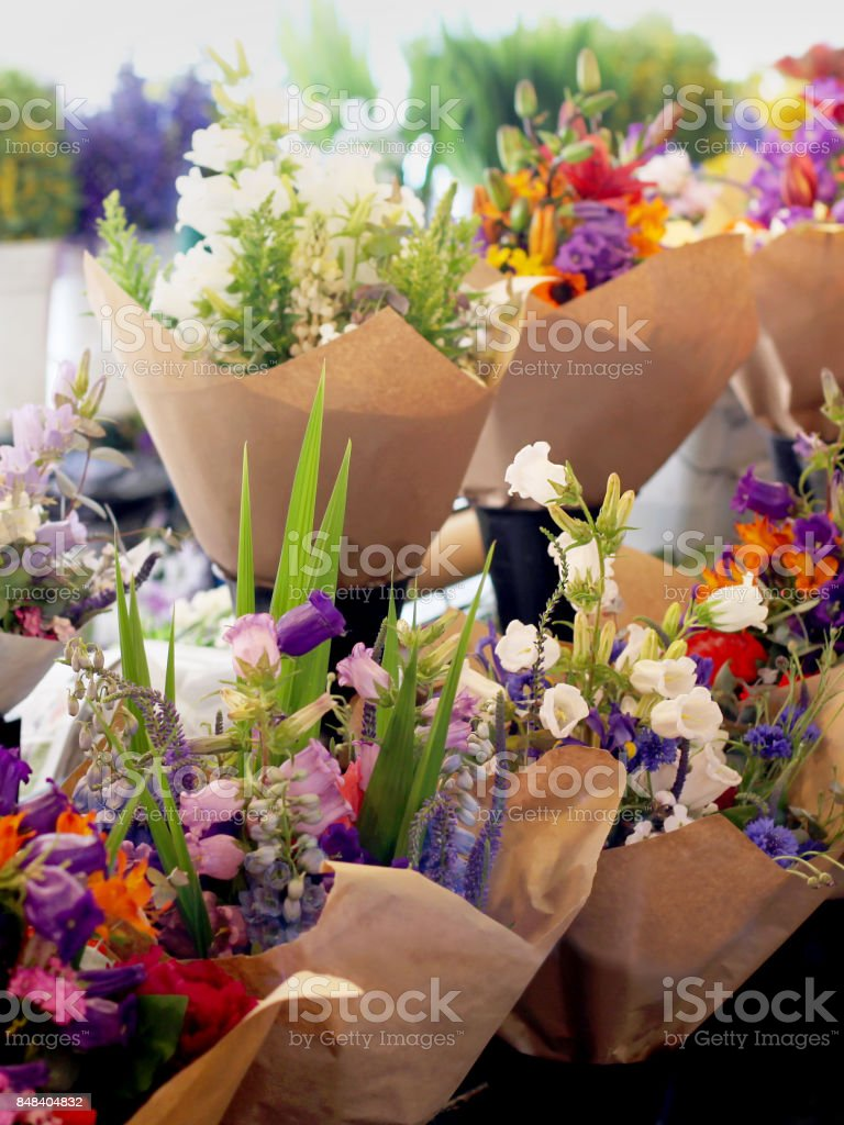 Vendor Sells Mixed Flower Bouquets Wrapped In Brown Paper Stock
