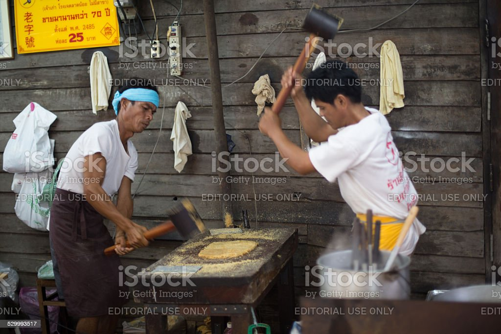 Vendors flatten peanut candy, Talad Noi, Bangkok, Thailand. stock photo