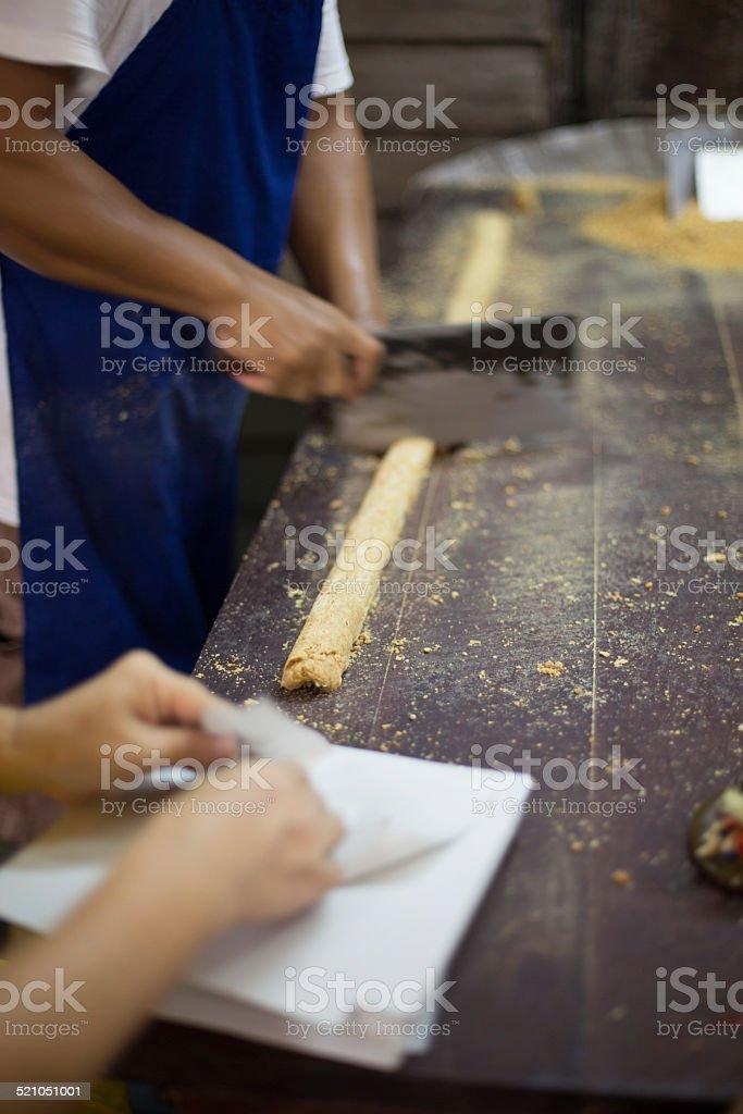 Vendors prepare peanut candy, Talad Noi, Bangkok, Thailand. stock photo