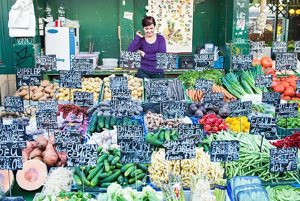 verkäufer verkauf von gemüs'im stall in den naschmarkt in wien - naschmarkt stock-fotos und bilder