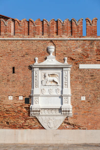 Venetian Arsenal, old shipyard, relief of Lion of Saint Mark on facade, Venice, Italy Venice, Italy - September  22, 2017: Venetian Arsenal, old shipyard, relief of Lion of Saint Mark on facade porta magna stock pictures, royalty-free photos & images