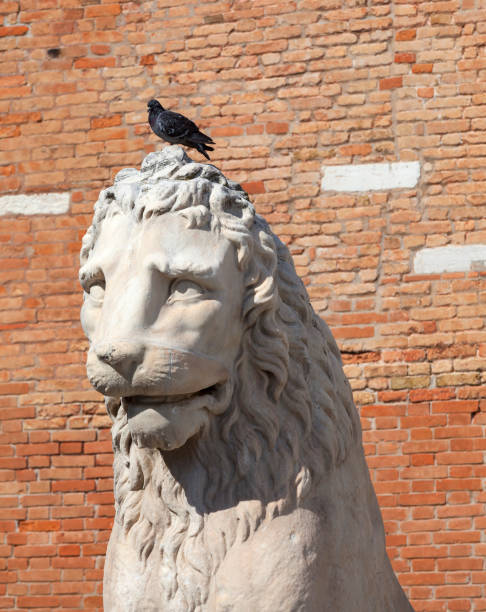 Venetian Arsenal, old shipyard, stone lion, Venice, Italy. Venice, Italy - September 22, 2017: Venetian Arsenal, old shipyard, stone lion. Construction of the Arsenal began in the 12th century, it was the largest industrial complex in Europe before the Industrial Revolution porta magna stock pictures, royalty-free photos & images