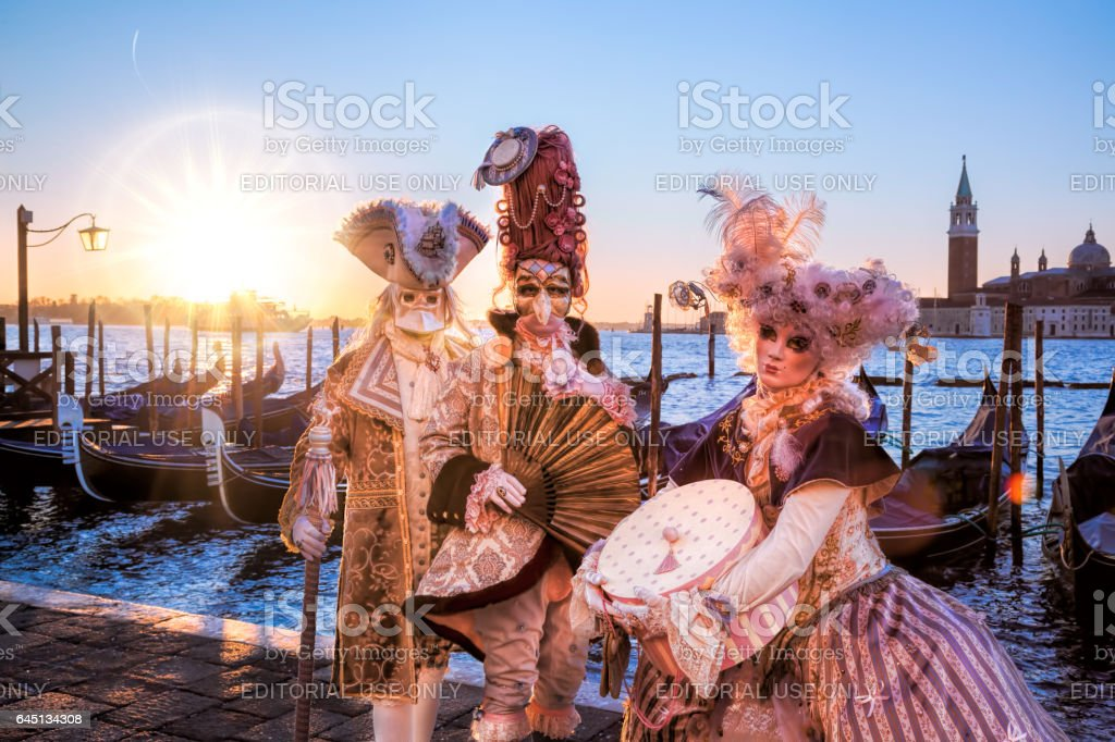 Venice, Italy- February 5, 2016. Venetian costumes pose in front of gondolas during the Venice Carnival days. The most  famous festival in the world. stock photo