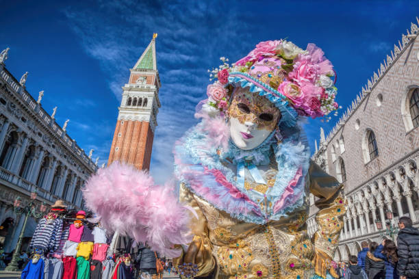 Venice, Italy- February 4, 2016. Venetian costumes pose on St. Mark square during the Venice Carnival days. The most  famous festival in the world. stock photo