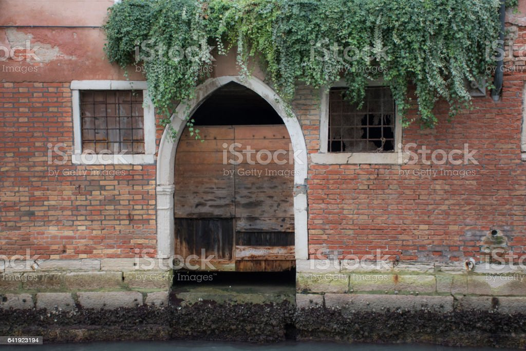 venetian door way onto canal which acts as boat ramp stock photo