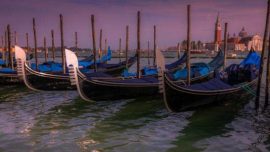 Venetian gondolas in San Marco pier and San Giorgio Maggiore at sunset, Venice, Italy