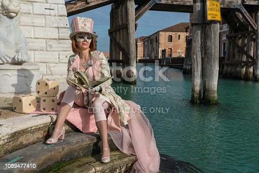 Venice, Italy - February 5, 2018: Venice Carnival Masks - Female mask wearing dressed in pink sitting at the Arsenale della Biennale di Venezia along canal with large book in her hands.