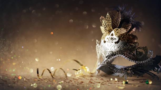 máscara veneciana en fondo de oro oscuro - fiesta de carnaval - carnaval fotografías e imágenes de stock