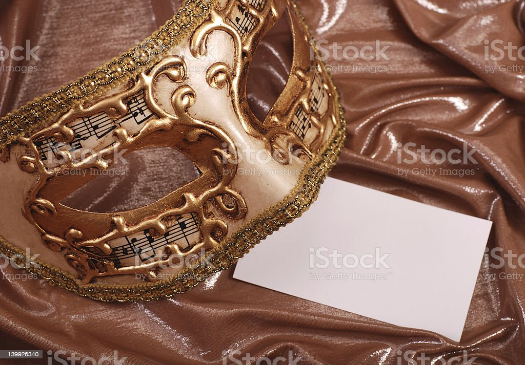venetian mask with blank note on gold silk background royalty-free stock photo