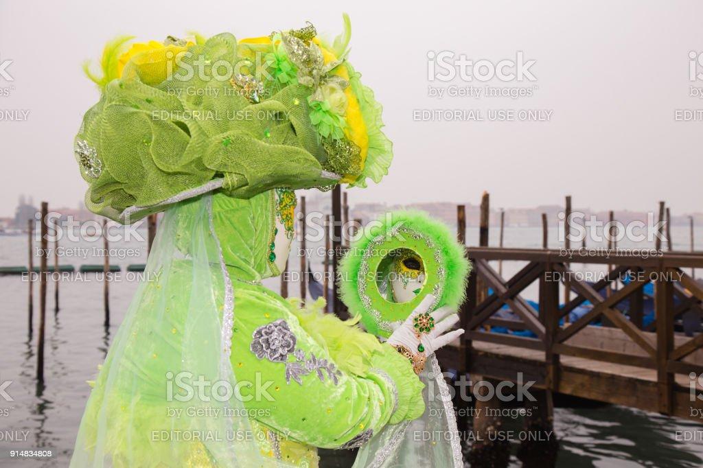 Venetian Masks in green dress with mirror and tradicional Venice Gondolas, Venice Carnival stock photo