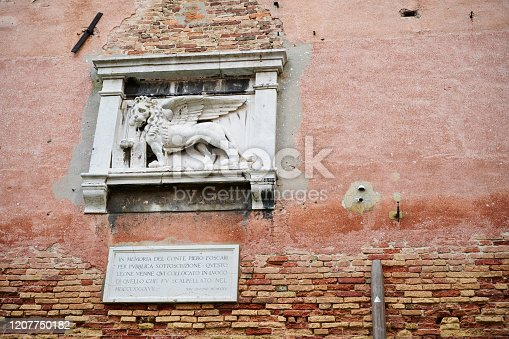 Sculpture of Venice winged lion on the external wall of an old building in Fondamenta dei Penini. Castello Sestier. Venice. Italy.