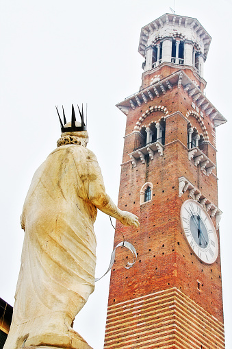 Veneto region, Verona, Italy - March 20, 2010 - Fountain statue of Madonna Verona (Fountain of our Lady Verona) with medieval tower of the Lamberti (Torre dei Lamberti) in background at Piazza delle Erbe (Market square).
