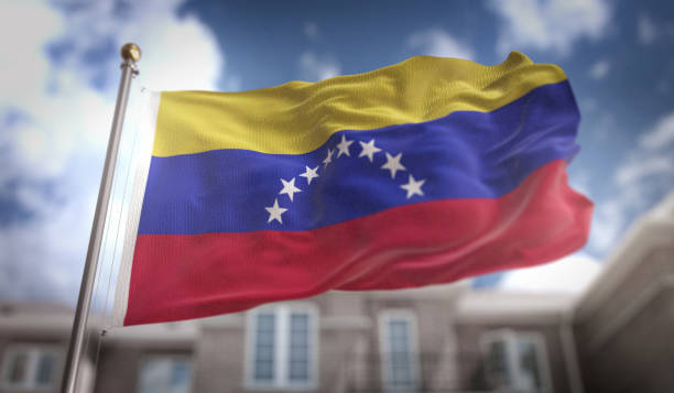 venezuela flag 3d rendering on blue sky building background - venezuela stock photos and pictures