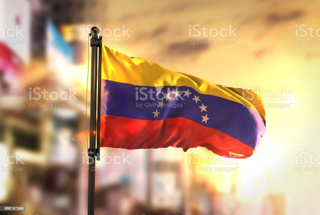 Bandera de Venezuela contra la ciudad borrosa de fondo en contraluz amanecer foto de stock libre de derechos