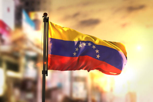 venezuela flag against city blurred background at sunrise backlight - venezuela stock photos and pictures