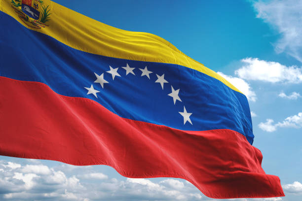 venezuela with coat of arms flag waving cloudy sky background - venezuelan flag stock photos and pictures