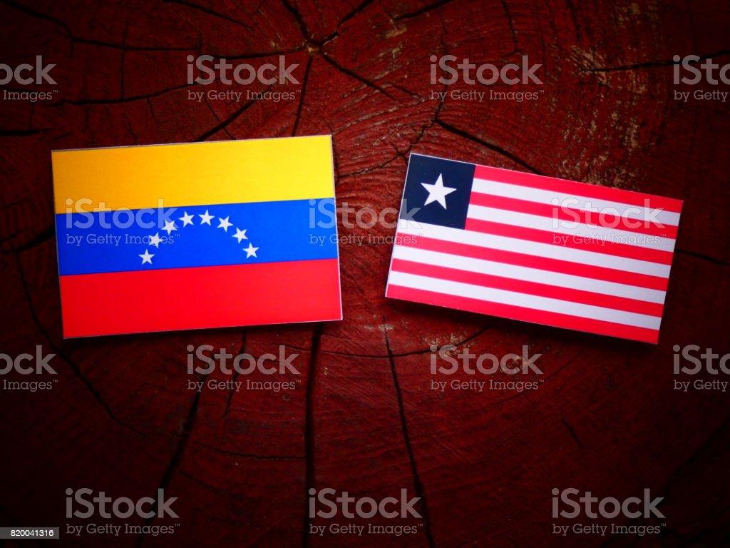 Venezuelan flag with Liberian flag on a tree stump isolated stock photo