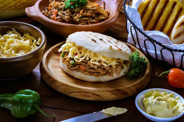 Nourriture traditionnelle vénézuélienne, Arepa au fromage râpé et viande (Pelua). Ingrédients sur une table dans une cuisine rustique. - Photo