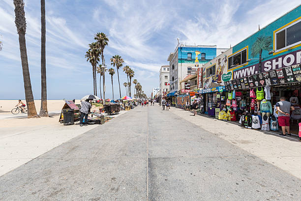 Venice Beach Boardwalk Editorial Los Angeles, California, USA - June 20, 2014:  Shops and tourists on the famously funky Venice Beach board walk in Los Angeles.   venice beach stock pictures, royalty-free photos & images