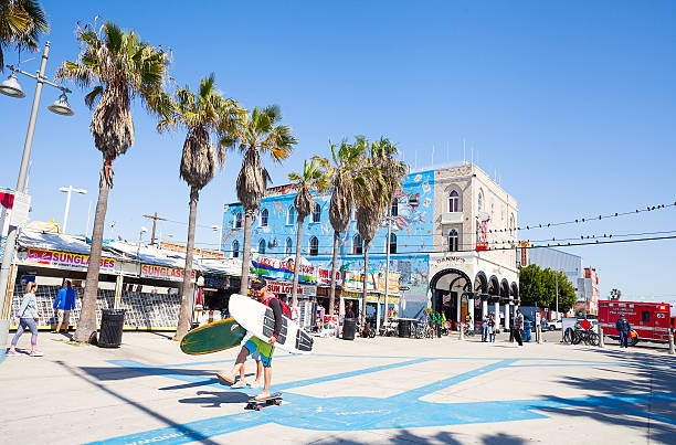 Venice Beach boardwalk, Los Angeles, California Venice, Los Angeles, California, USA - March 12, 2016: Two men with surfboards walking at the famous Venice Beach promenade. The boardwalk features performers, vendors, restaurants, and artists selling their craft.  venice beach stock pictures, royalty-free photos & images