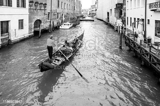 Venice canal Rio Dei Greci with water taxis and a Gondola heading towards the tower of San Giorgio Dei Greci.