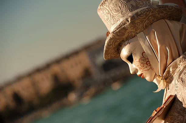 Venice Carnival 2014 Venice, Italy - February 24, 2014: On the photo we can see portrait of female masked person with traditional venice carnival disguise and hat in beige and gold colors. She posing against blue sky at see side. 2014 stock pictures, royalty-free photos & images