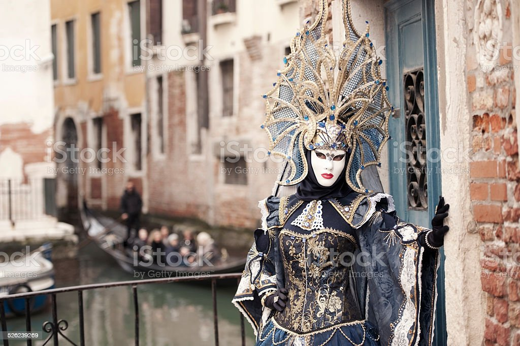 Venice Carnival 2014 Attractive masked person in glamourous carnival costume and attractive headwear posing at one of numbered canals of Venice, Italy. On the outfocused background we can see gondola with tourists. Toned horizontal image. 2014 Stock Photo