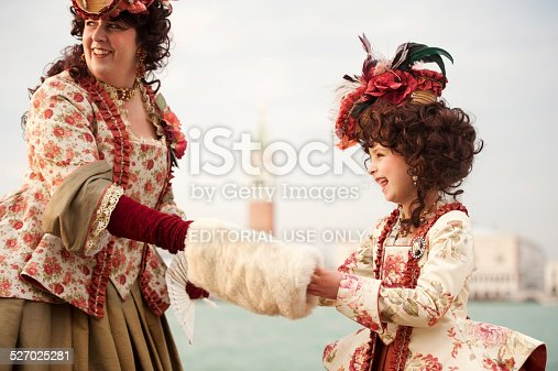 Venice, Italy - March 3, 2014: The photo was taken during the famouse carnival in front the church San Giorgio Maggiore in Venice. We can see attractive adult woman with her daughter  who wearing traditional carnival costume and attractive headdress in red and beige color. Venice, Italy, Europe.