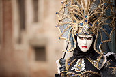 Portrait of an attractive masked female person in blue carnival costume and amazing headdress posing at stone arch in Venice, Italy.
