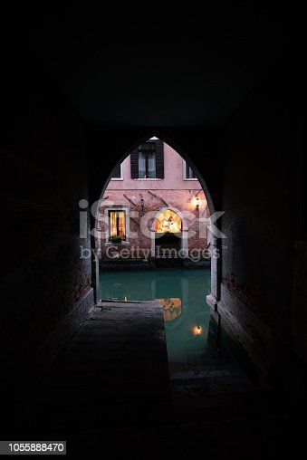 Venice dark streets at the morning. Window with the light. Vertical view