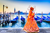 Venice, Italy - 9th February 2018: Carnival of Venice, beautiful mask at Piazza San Marco with gondolas and Grand Canal.