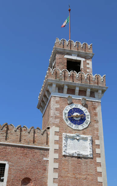 Venice Italy clock tower of an ancient palace called Arsenale Venice Italy high clock tower with italian flag of an ancient palace called Arsenale porta magna stock pictures, royalty-free photos & images