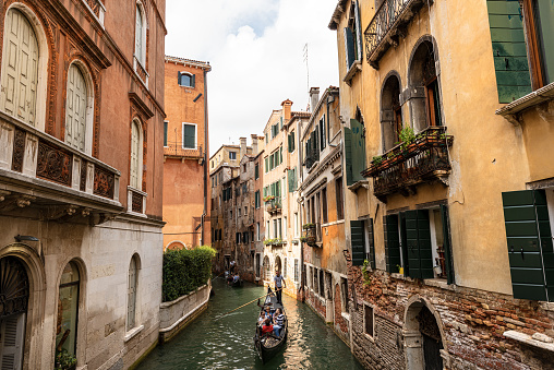 Venice, Veneto, Italy - Sept 13th, 2015: Two gondolas with gondoliers and tourists in a narrow canal of the Venetian lagoon, typical rowing boat. Sightseeing tour in the famous city. Veneto, Italy, Europe. The gondola is a traditional, flat-bottomed Venetian rowing boat, well suited to the conditions of the Venetian lagoon. It is similar to a canoe, except it is narrower. It is propelled by a gondolier, who uses a rowing oar, which is not fastened to the hull, in a sculling manner and acts as the rudder.