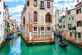 Venice, Italy - April, 3, 2019: Scenic canal with old beautiful architecture in Venice, Italy.