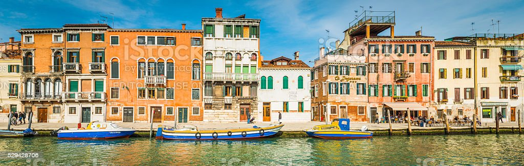Venice local people and colourful boats beside canal villas Italy stock photo