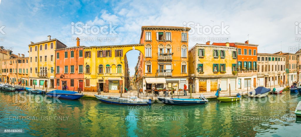 Venice locals and boats beside colorful villas canal panorama Italy stock photo