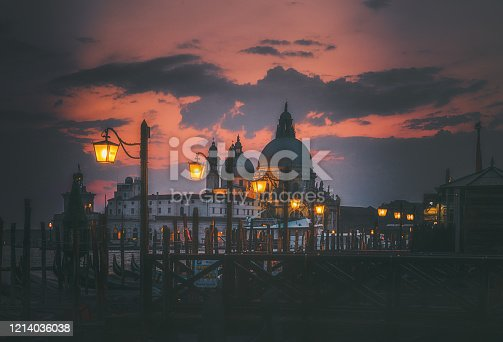 Scenic view of Santa Maria della Salute Basilica and illuminated street lamps standing near the grand canal with dramatic cloudy sunset sky in Old town of  Venice, Italia