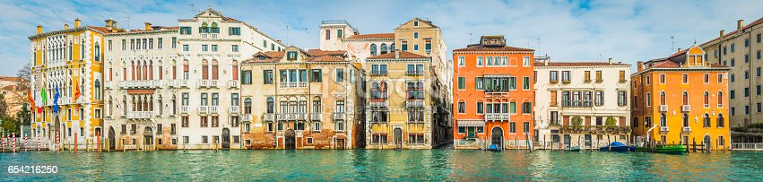 Colourful villas and palazzo reflecting in the tranquil waters of the Grand Canal in the Academia district of Venice, Italy.