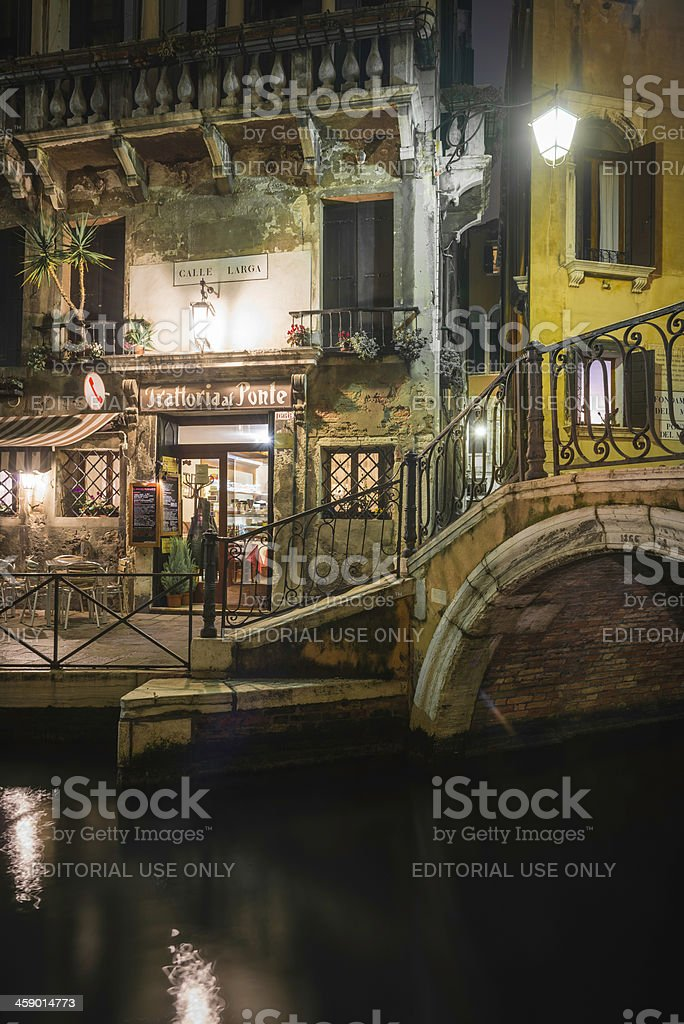 Venice quaint trattoria restaurant beside quiet canal at night Italy stock photo