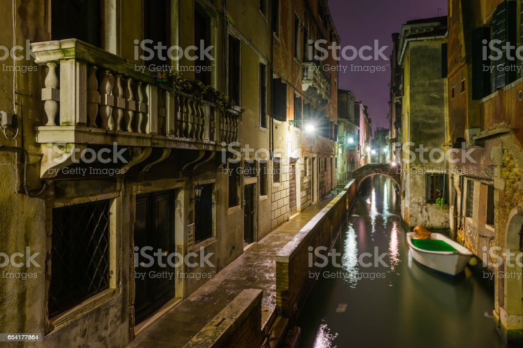 Venice quiet canals alleyways illuminated by lamplight at night Italy stock photo