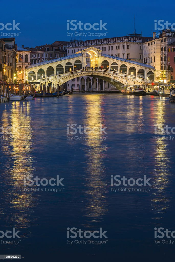 Venice Rialto Bridge illuminated at dusk over Grand Canal Italy stock photo