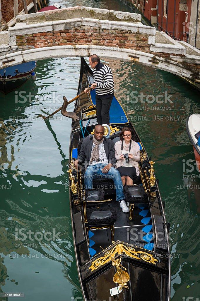 Venice tourist couple on gondola ride along narrow canal Italy royalty-free stock photo
