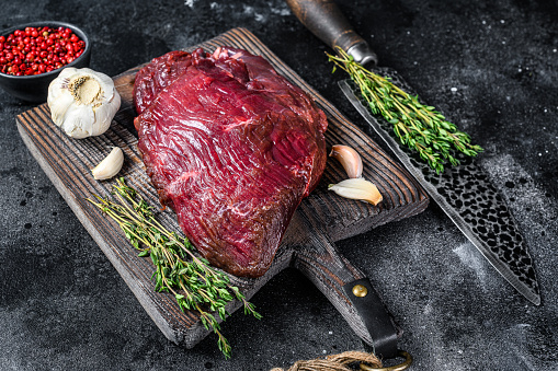 Venison raw deer meat on a cuuting board with herbs. Black background. Top view.