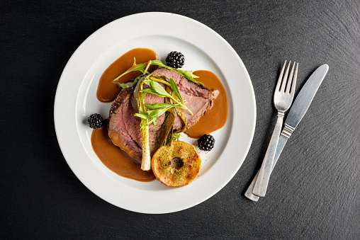Overhead dish of venison with apple and seasonal vegetables. Colour, horizontal with some copy space, photographed on location at a restaurant on the island of Moen in Denmark.