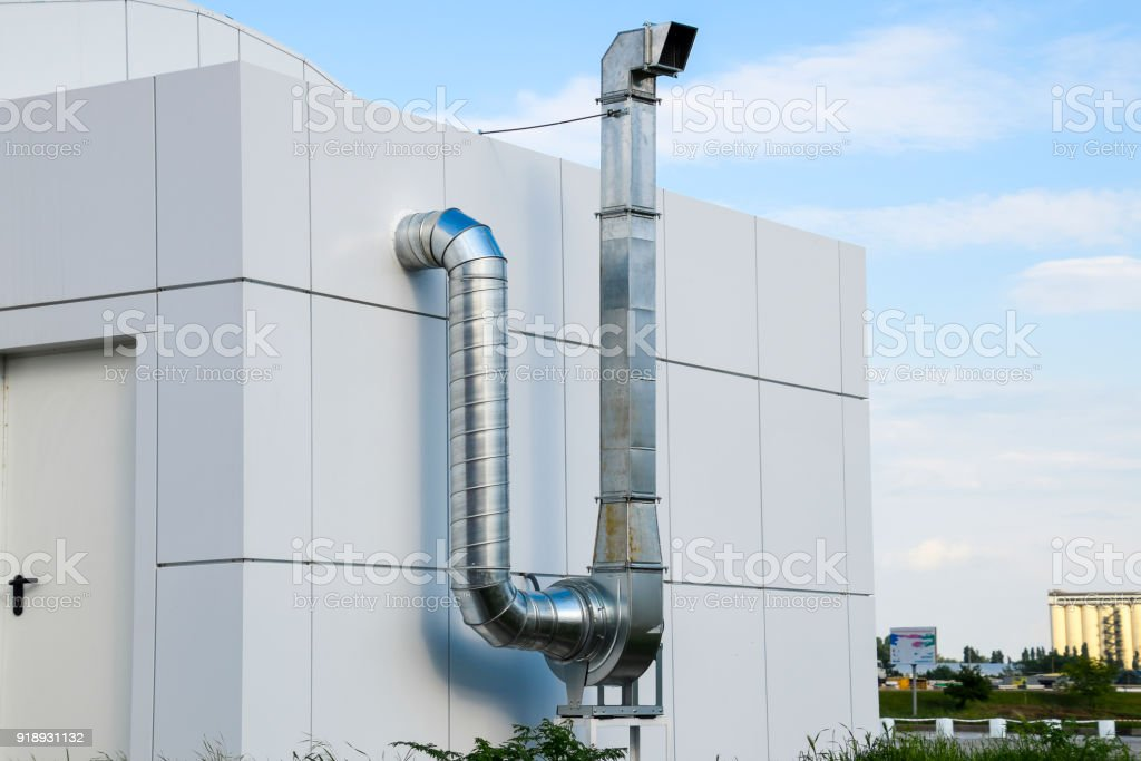 Ventilation hood with a pipe behind the cafe building. stock photo