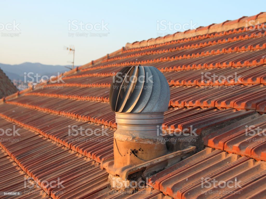 Ventilation Metal Chimney on Shingle Roof with View stock photo