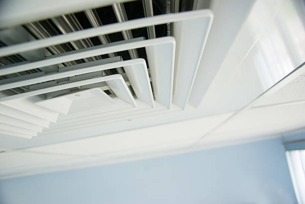 ventilation system; air condition vent in office ceiling close up stock photo
