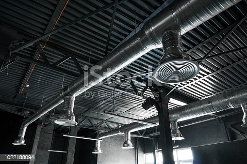 1132163701istockphoto Ventilation system on the ceiling of large buildings. Ventilation pipes in silver insulation material hanging from the ceiling inside new building. 1022188094