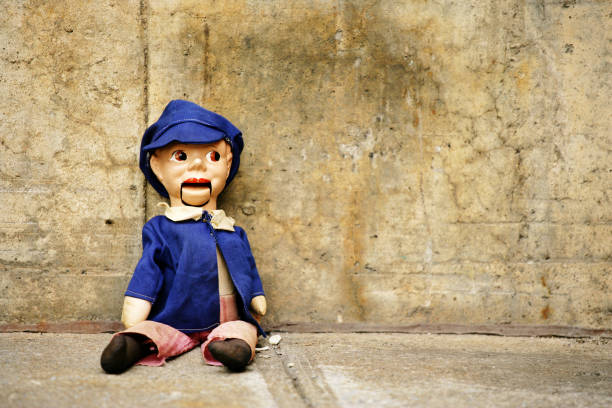 Ventriloquist Dummy Sitting Against Concrete Wall  ventriloquist's dummy stock pictures, royalty-free photos & images