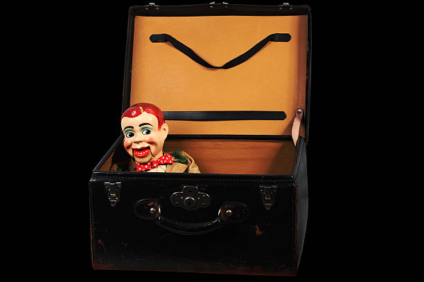 Ventriloquist's Doll in a luggage 1950's Vintage Ventriloquist's Dummy in an old luggage in a dark room. ventriloquist's dummy stock pictures, royalty-free photos & images